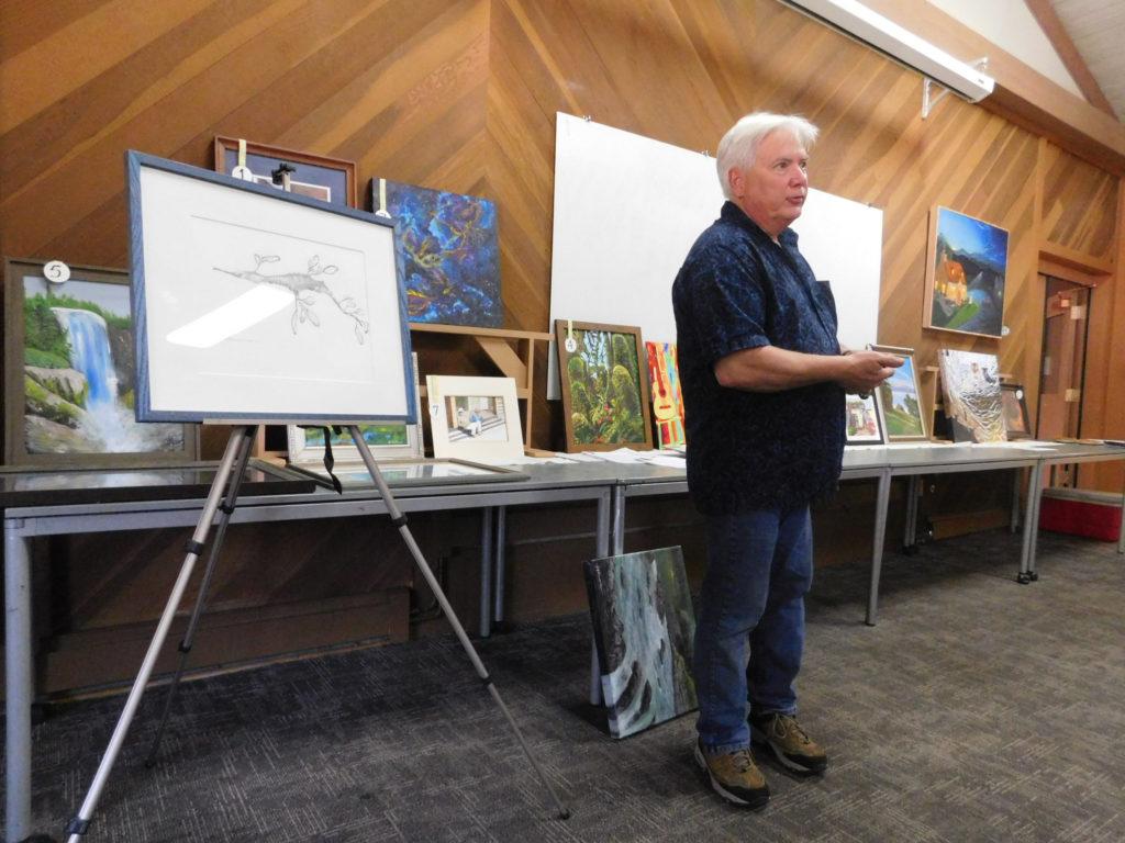 Artist Jeff Bramschreiber during a demonstration at the Campbell Artists' Guild on framing artworks